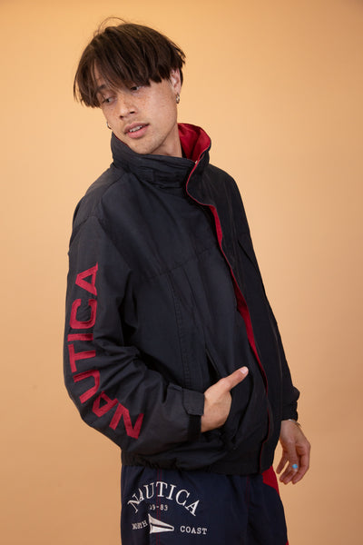 This thick anorak-like jacket is black with a red foldable collar and red inner lining Has red Nautica branding on the right arm and neckline and 'competition' in white on the left arm. Has zip up pockets and both zip and velcro closures.
