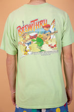 Load image into Gallery viewer, ight green single stitch tee with BrewThru Outer Banks NC printed on the left chest. On the back, a large colourful print of a guy playing guitar, some animals dancing, a chilly bin dated '99 and BrewThru printed across.
