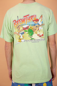 ight green single stitch tee with BrewThru Outer Banks NC printed on the left chest. On the back, a large colourful print of a guy playing guitar, some animals dancing, a chilly bin dated '99 and BrewThru printed across.