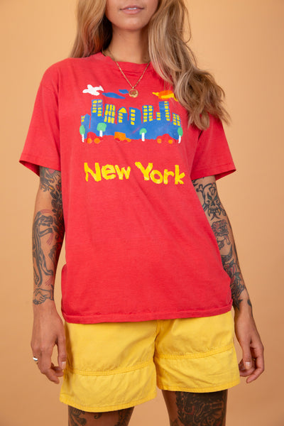 red single-stitch tee with a cute cartoonish drawing of New York on the front