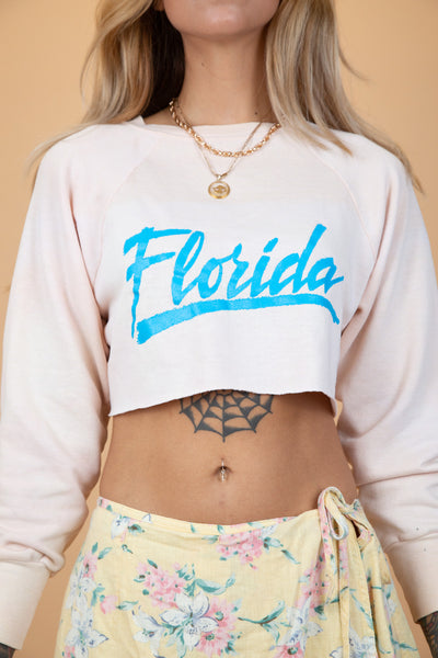 "pink cropped sweater with blue ""florida"" on the front"