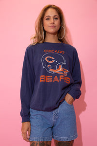 Navy blue in colour, this jumper has a large orange 'Chicago Bears' spell-out across the front with an orange and white helmet print on the front.