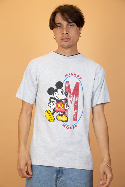 This grey tee has a large Mickey Mouse print on the front with a large red 'M' next to it. Finished off with blue foldable sleeves and a blue double-layered collar.
