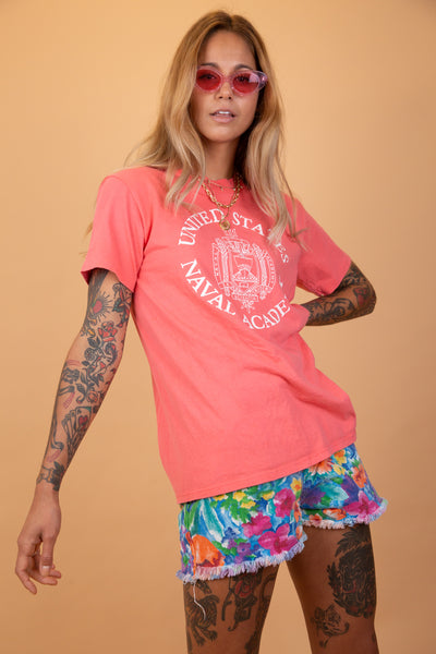 pink single stitch tee with white graphic on the front that says