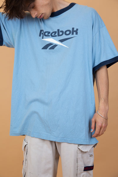 Light blue Reebok ringer tee with dark blue along the neckline and arms. Reebok printed in navy blue on the front with the Reebok logo below.