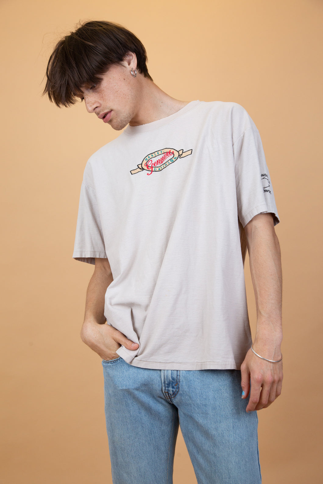 Light brown, creamy colour single-stitch tee in a ribbed, textured material with an embroidered appliqué of 'Harley Davidson Genuine' centred on the front. Repping Wisconsin H.D on the left sleeve.
