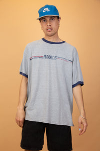 Grey Nike ringer tee with contrasting navy blue rings on the neckline and sleeves. On the front, a retro Nike spell-out with blue and red stripes.