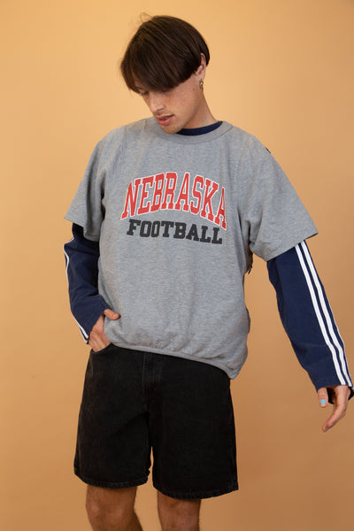 This Adidas short-sleeved sweater has 'Nebraska Football' printed on the front in red and black, zips on the sides and a red netted material under the zips. Adidas rubber branding on the left shoulder.