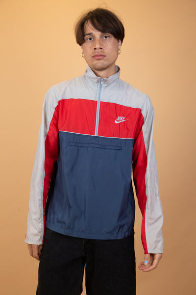 This thin rain jacket-like pullover is grey, red and blue with a quarter zip, a horizontal zip-up pocket, a foldable collar and embroidered branding on the left chest.