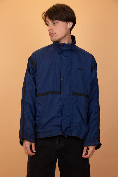 This light anorak-feel jacket is navy blue in colour with black stripes, black branding and black domes with a black inner lining and foldable collar.