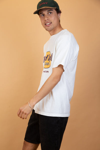 Off-white in colour with a yellow and maroon Hard Rock Cafe logo on the front and repping Cancun below. Ribbed neckline with a tall fit.