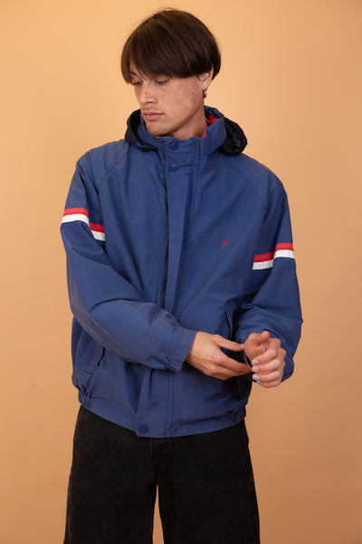 Blue anorak-like jacket with a red inner collar and red Nautica branding on the left chest. Has red and white striped sleeves and back, zip-up pockets and a closing zipline fitted with domes. Has a built in hood.