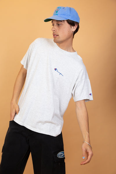 Light grey in colour with Champion branding on the left chest and left sleeve, single-stitching and a stretched out neckline that adds to the baggy fit.