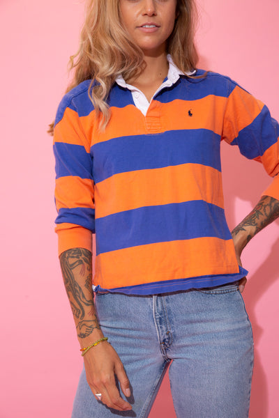 Horizontally striped in blue and orange, this polo style tee has three quarter length arms, a white collar and matching white buttons. Finished off with navy blue embroidered Ralph Lauren logo on the left chest