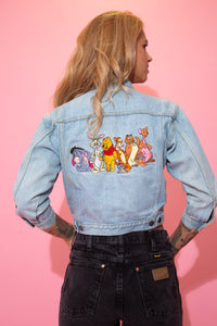 Light wash blue, this denim jacket has light brown stitching, double breast and side pockets, branded buttons, three quarter length arms and a large embroidered print of Winnie the Pooh and the Hundred Acre Wood gang on the back.