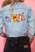 Load image into Gallery viewer, Light wash blue, this denim jacket has light brown stitching, double breast and side pockets, branded buttons, three quarter length arms and a large embroidered print of Winnie the Pooh and the Hundred Acre Wood gang on the back.