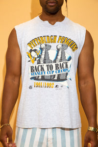 Grey in colour in a singlet style, this tee has a large yellow 'Pittsburgh Penguins' spell-out across the top with a print of 2 Stanley Cups behind a banner reading 'Back to Back Stanley Cups.' Dated 1992.