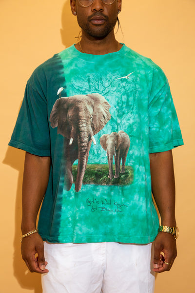This tee is a tie-dye print with a vertical contrast between dark green and a lighter green. With a large print of two elephants on the front and 'York's Wild Kingdom York Beach Maine' printed below.