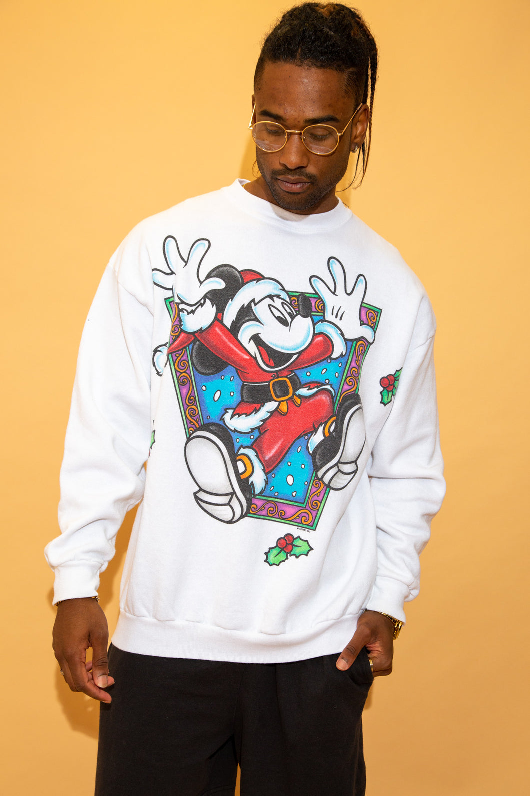 White in colour with a large print of Mickey Mouse in a Santa Clause outfit jumping out of an abstract print!