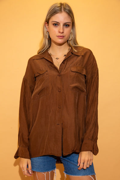 Brown in colour with a silky material, matching brown buttons and two chest pockets.