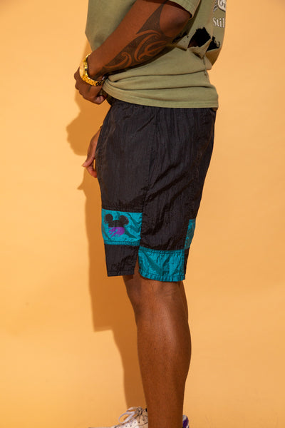 These shorts have a nylon feel, a comfy fit with an adjustable waistline. Black in colour with a teel-coloured block pattern on the left leg and a black and purple smudged looking Mickey Mouse symbol.