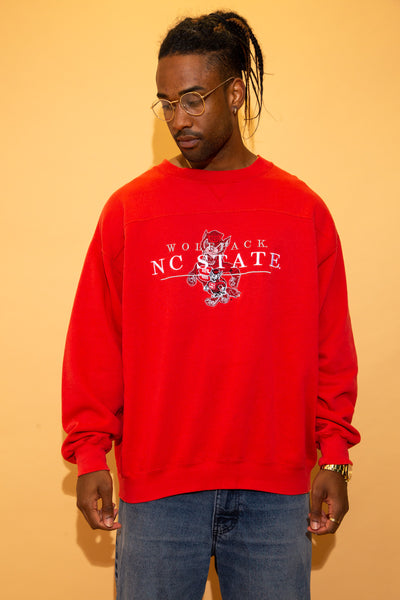 Red in colour in an oversized, baggy fit, this jumper has an embroidered Wolfpack mascot on the front with 'Wolfpack NC State' embroidered across in grey and white.