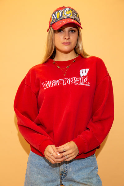 This thick oversized sweater is red in colour with a white outlined Wisconsin Badgers spell-out and a large W logo.