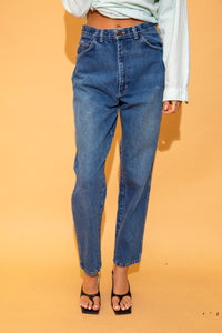 the model wears dark wash relaxed fit jeans