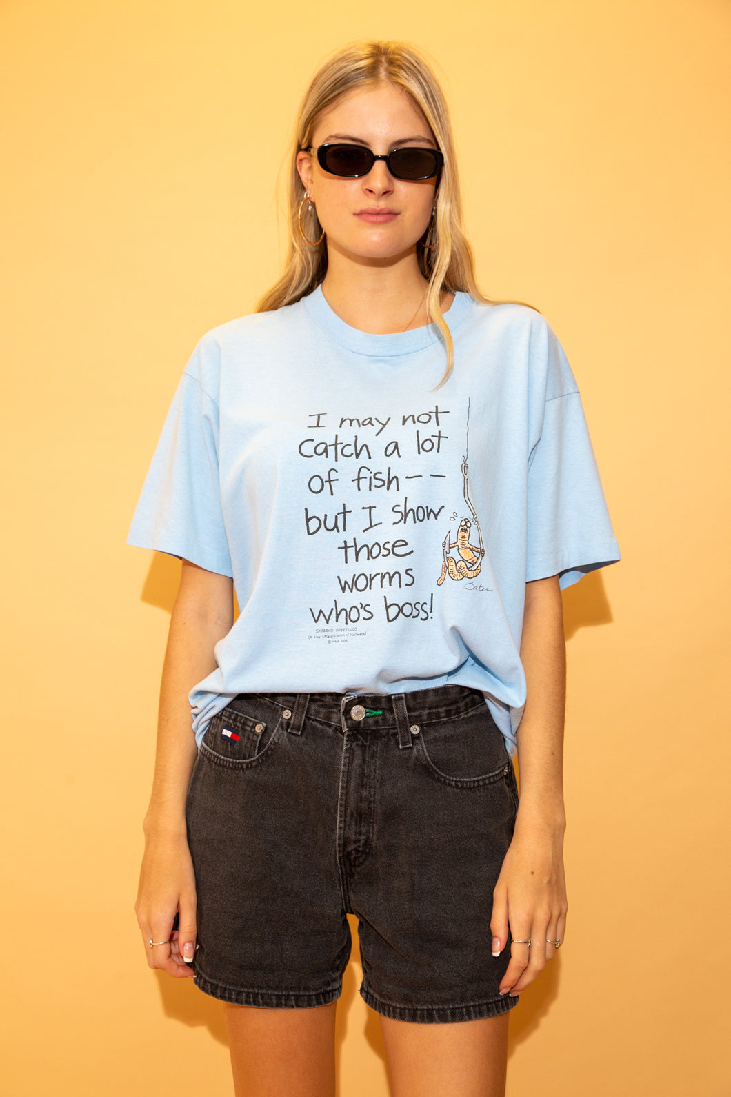 This single stitch tee is light blue with 'I may not catch a lot of fish - but I show those worms whose boss' printed in black across the front of the tee. Has a print of a scared worm on a hook.