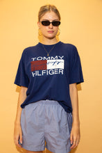 Load image into Gallery viewer, This Bootleg Tommy tee is blue in colour with a white Tommy Hilfiger spell-out and the red and white Tommy Hilfiger logo in the middle.