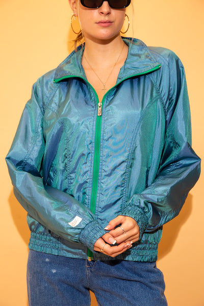 Blue with a shiny purple/green tinge and in a lightweight material, this jacket has a green zip, foldable collar, pockets and Nike branding on the right arm and zip.