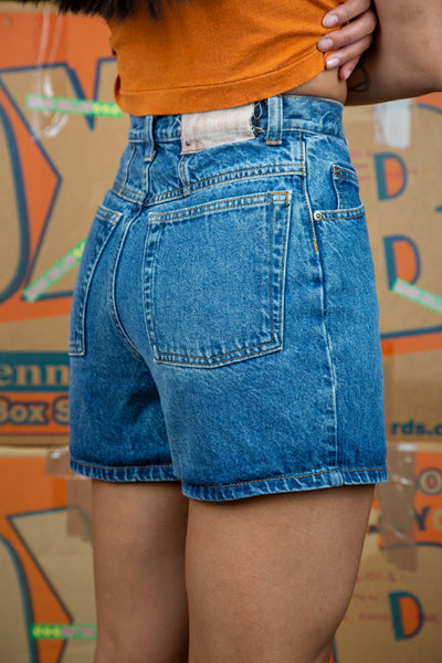 the model wears mid blue washed denim shorts