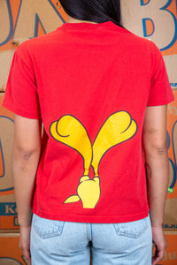the model wears a red tee with a tweety bird graphic on the front and back