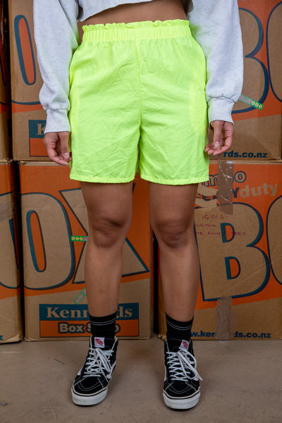 the model wears neon yellow shorts