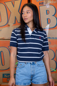 the model wears a navy and white striped polo