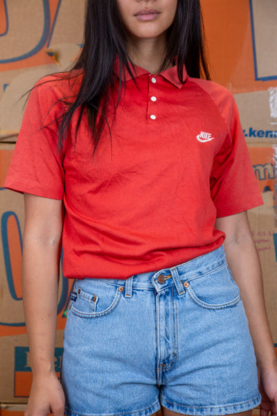 the model wears a red nike white tag polo