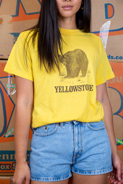 the model wears a yellow tee with a yellowstone graphic on the front