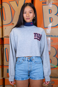 the model wears a grey sweater with a navy turtleneck detail