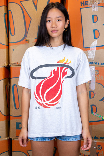 the model wears a grey tee with a miami heat logo on the front