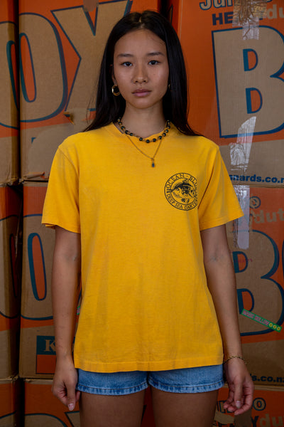 the model wears a yellow tee with an ocean pacific logo graphic on the front and back