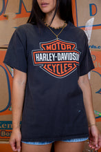 Load image into Gallery viewer, the model wears a black tee with harley davidson graphics on the front and back