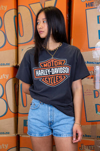 the model wears a black tee with harley davidson graphics on the front and back