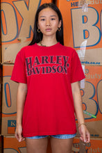 Load image into Gallery viewer, the model wears a red harley davidson tee with an indial chief graphic on the back