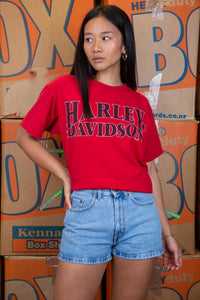 the model wears a red harley davidson tee with an indial chief graphic on the back