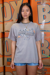 the model wears a grey tee with harley graphics on the front and back