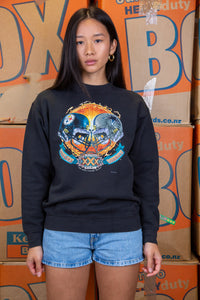 the model wears a black sweater with a super bowl xxx logo on the front