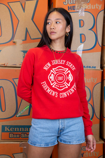 the model wears a red sweater with a new jerseys state firemans convention on the front