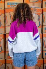 Load image into Gallery viewer, Grey in colour, this sweater is in a quarter-zip style with a fuchsia pink top half and dark purple striped waist and arms.