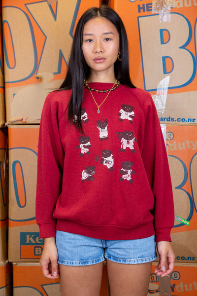 the model wears a maroon sweater with bears graphics on the front
