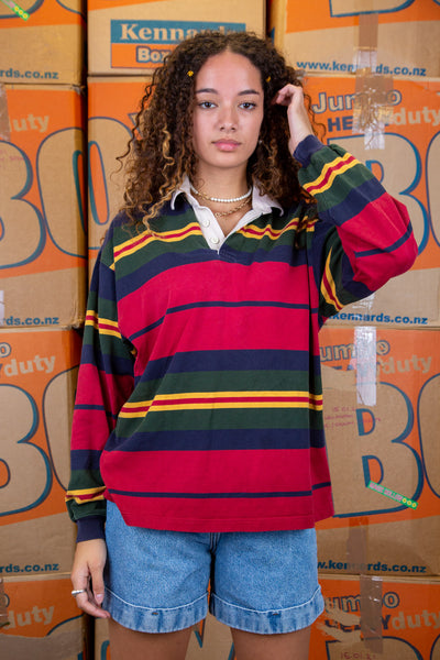the model wears a striped rugby jumper